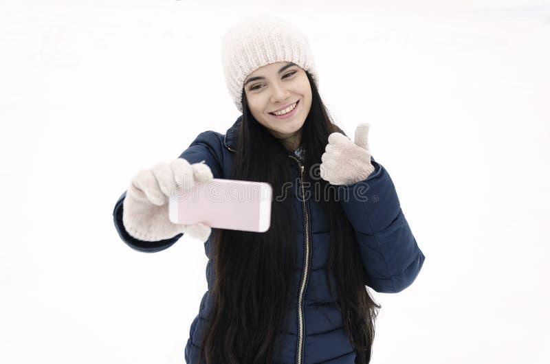 La ragazza con uno smartphone chiama un amico nel parco fotografia stock libera da diritti
