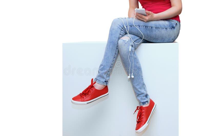 La ragazza con uno smartphone in sue mani si siede su una scatola bianca isolato bianco immagini stock