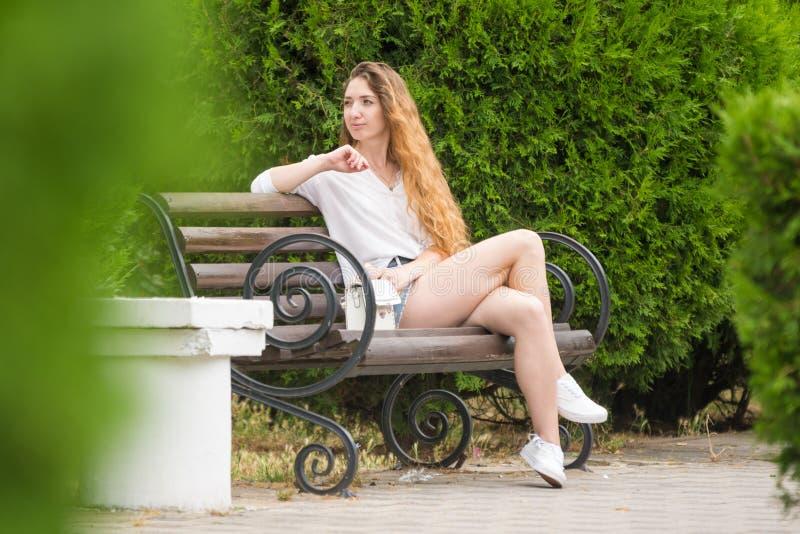La ragazza considera i lati che riposano su un banco di parco fotografia stock