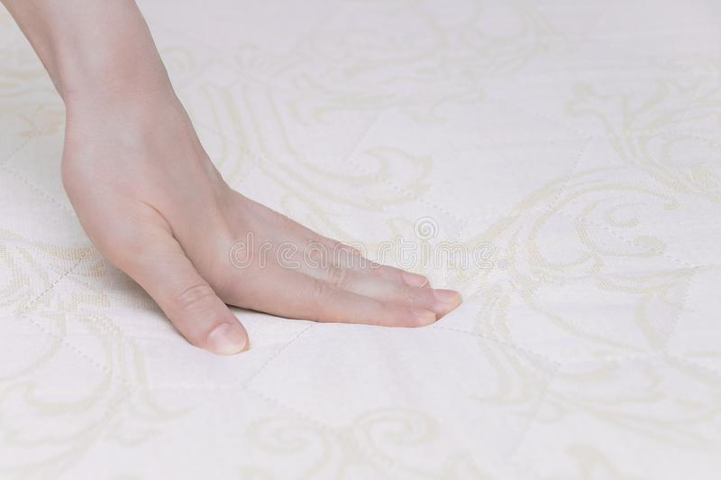 La ragazza controlla con la sua mano la rigidità del materasso per vedere se c'è il letto immagine stock