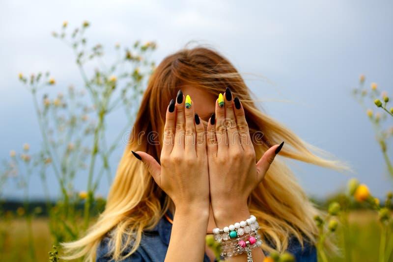La ragazza copre il suo fronte di sue mani fotografia stock