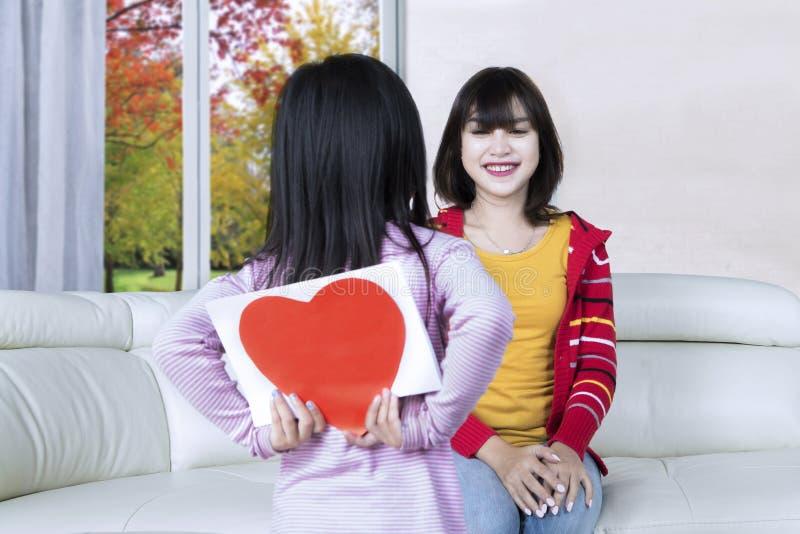 La ragazza dà a sua madre una cartolina d'auguri immagine stock libera da diritti
