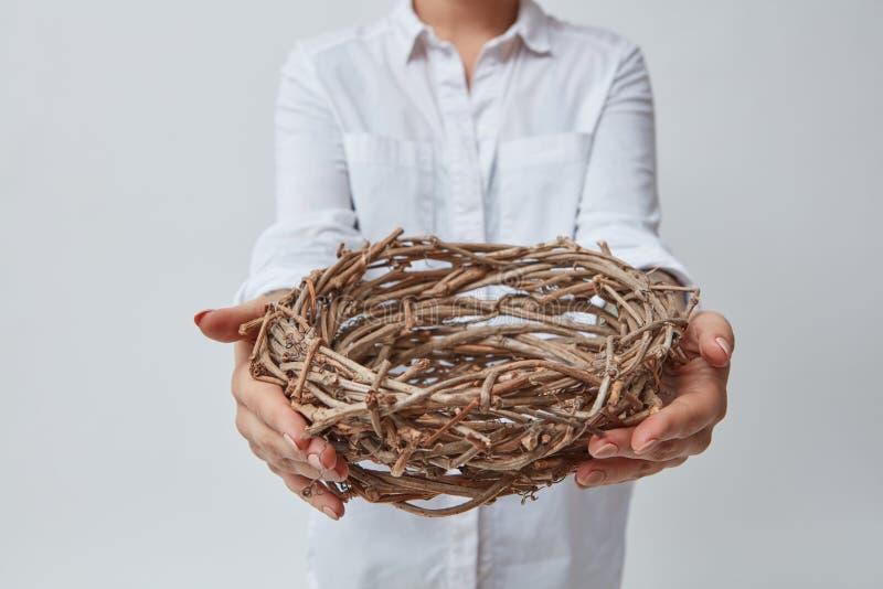 La ragazza dà un nido dei ramoscelli fotografie stock libere da diritti