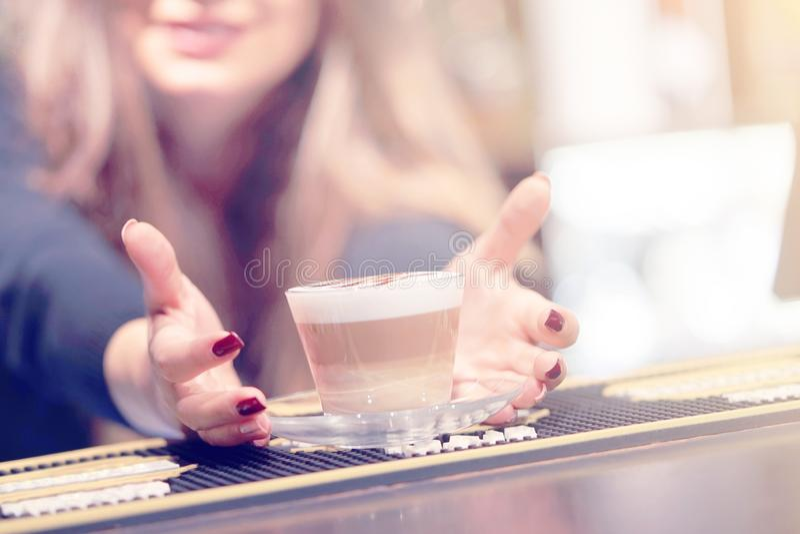 La ragazza dà una tazza di caffè-cappuccino fotografia stock libera da diritti