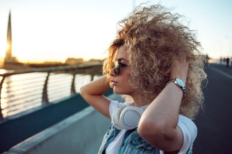 La ragazza d'avanguardia con le grandi cuffie e gli occhiali da sole su una città camminano, ritratto della giovane donna nel pro immagine stock