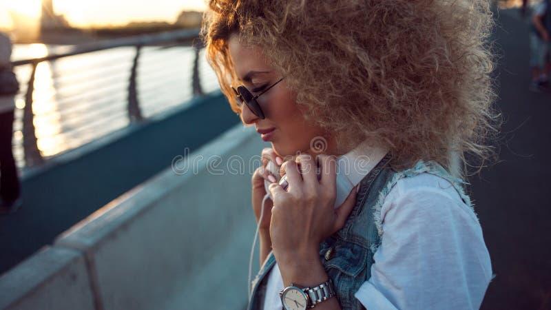 La ragazza d'avanguardia con le grandi cuffie e gli occhiali da sole su una città camminano, ritratto della giovane donna nel pro fotografie stock libere da diritti