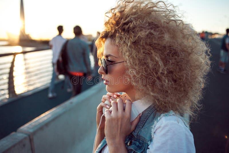 La ragazza d'avanguardia con le grandi cuffie e gli occhiali da sole su una città camminano, ritratto della giovane donna nel pro fotografia stock