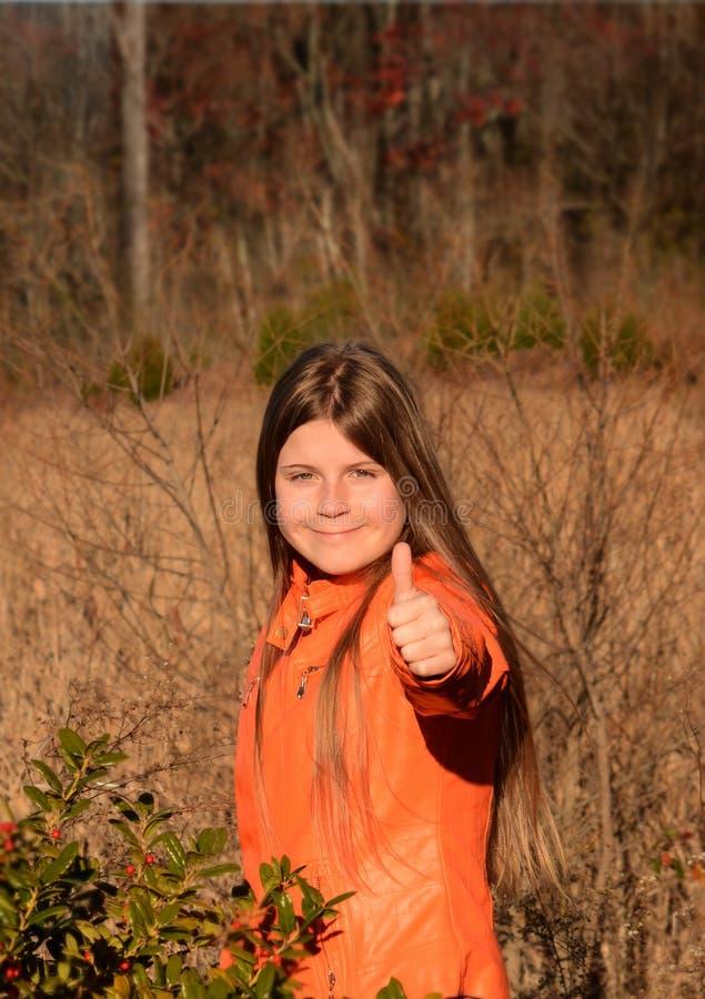 La ragazza d'escursione felice che mostra i pollici aumenta il segno immagine stock