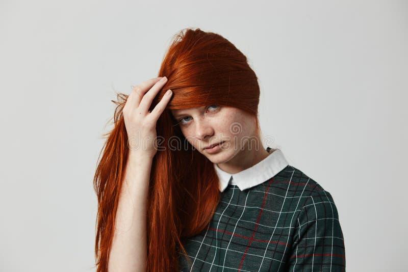 La ragazza dai capelli lunghi della bella testarossa in un vestito a quadretti verde chiude il suo fronte con i suoi capelli sui  fotografia stock