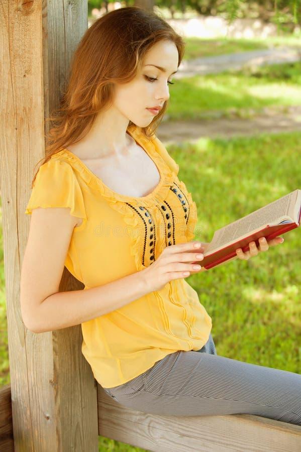 La ragazza dai capelli lunghi legge il libro fotografia stock libera da diritti