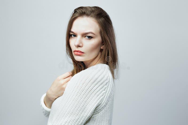 La ragazza dai capelli lunghi splendida in un maglione tricottato bianco sta posando sui precedenti bianchi nello studio fotografia stock
