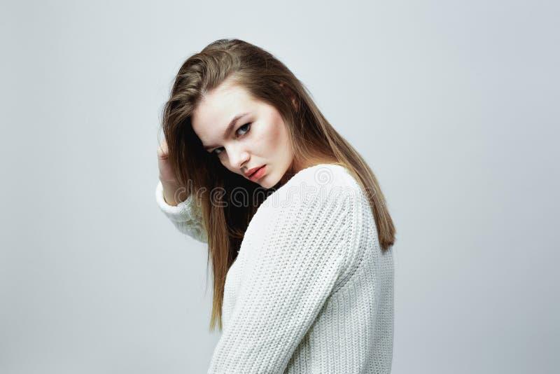 La ragazza dai capelli lunghi splendida in un maglione tricottato bianco sta posando sui precedenti bianchi nello studio fotografie stock libere da diritti