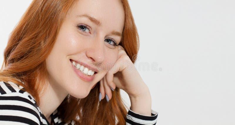 La ragazza dai capelli rossi con la fine sul macro fronte ed i denti bianchi perfetti sorridono isolato su fondo bianco Bellezza  fotografie stock libere da diritti
