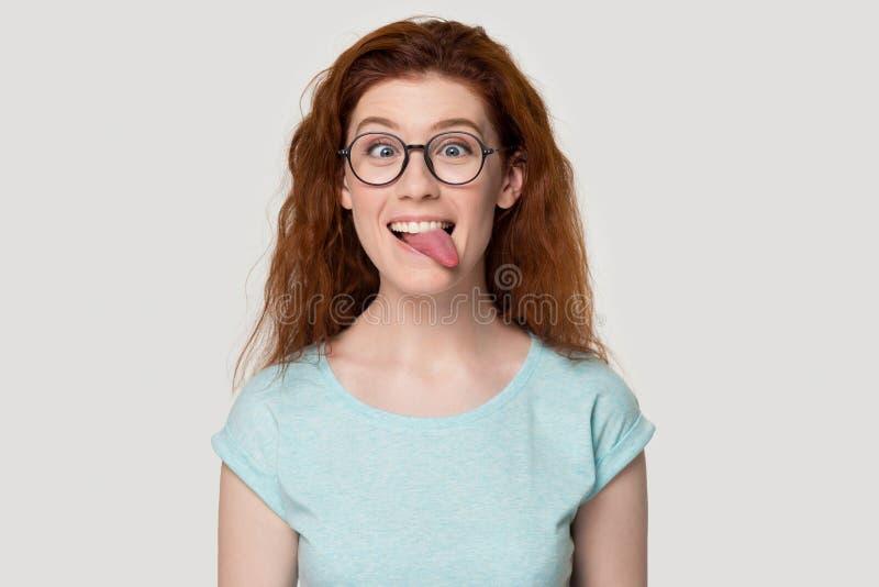 La ragazza dai capelli rossi divertente in vetri gioca la lingua di mostra puerile fotografia stock libera da diritti