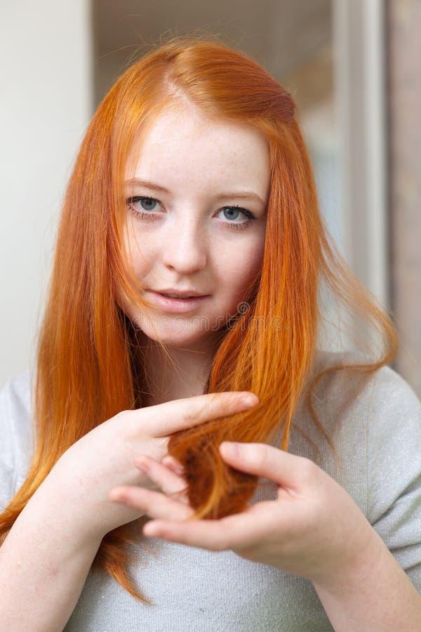 La ragazza dai capelli rossi esamina le punte di capelli fotografia stock libera da diritti