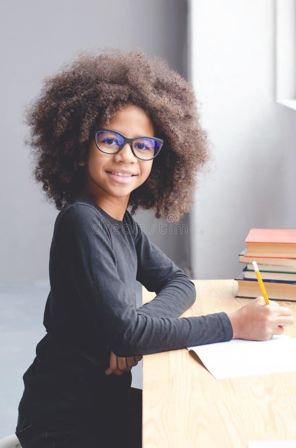 La ragazza dalla carnagione scura che si siede alla tavola insegna alle lezioni immagini stock