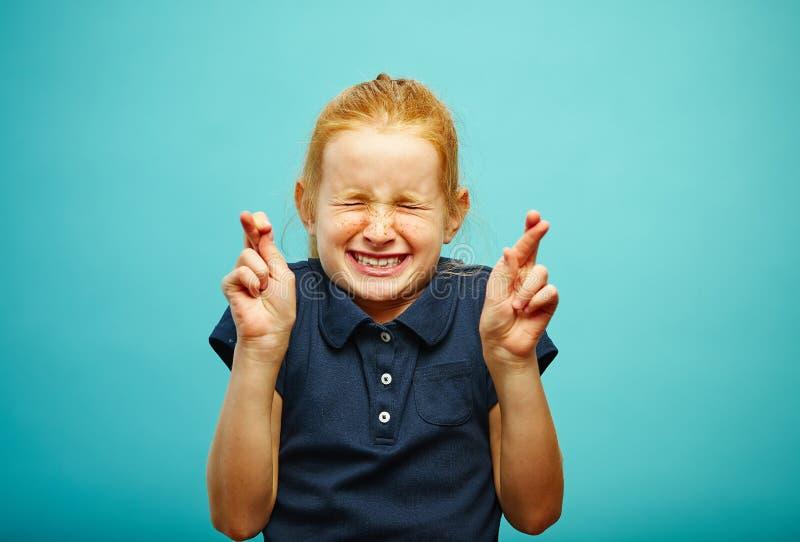 La ragazza dei bambini strettamente chiusa il suo osserva e messo le dita attraversate, fa un desiderio, crede nel sogno, esprime fotografia stock
