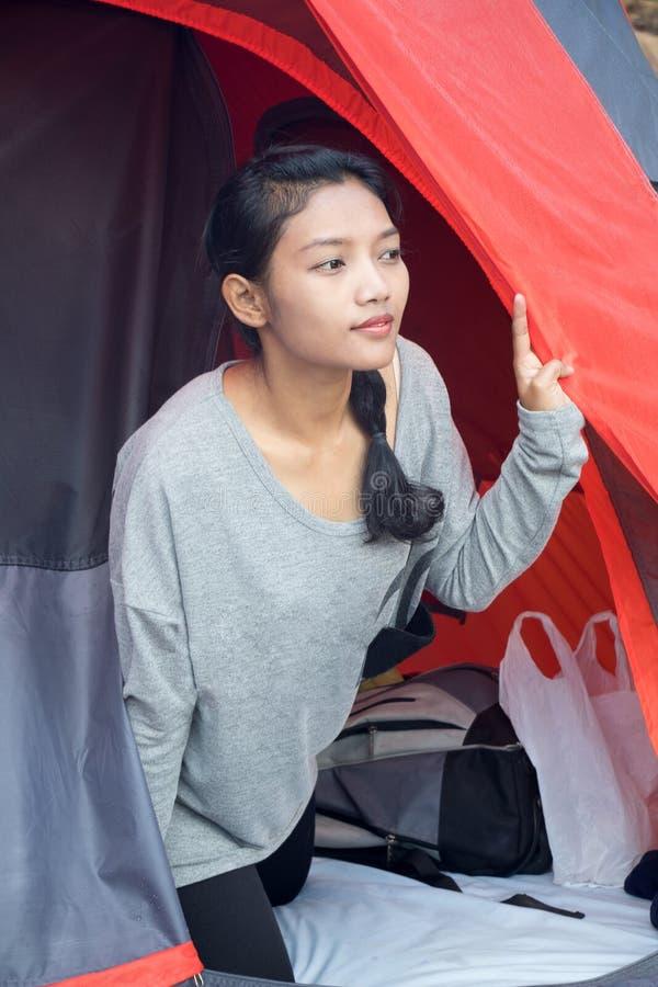 La ragazza dei campeggiatori guarda da una tenda fotografie stock