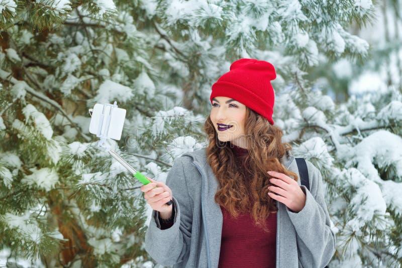 La ragazza dei pantaloni a vita bassa fa l'inverno del selfie fotografia stock