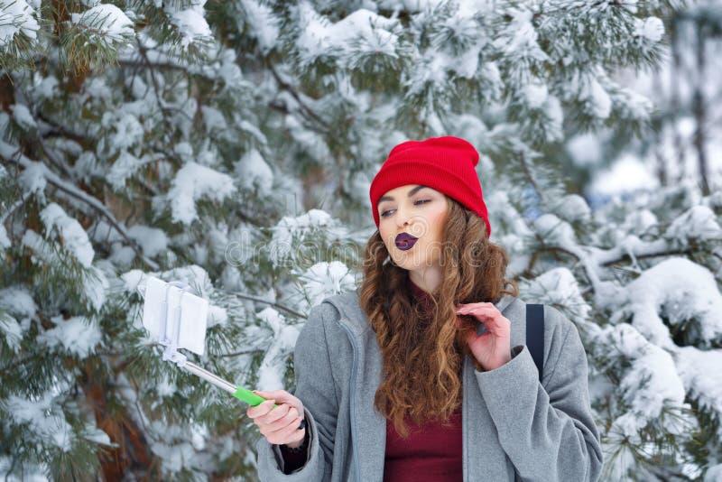 La ragazza dei pantaloni a vita bassa fa l'inverno del selfie immagine stock