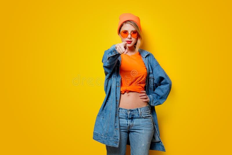 La ragazza dei pantaloni a vita bassa in jeans copre con i vetri arancio immagine stock