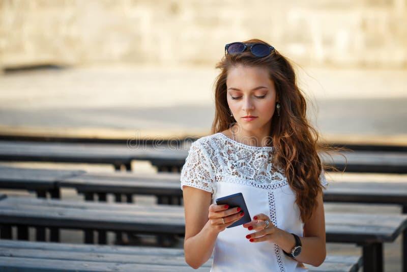 La ragazza dei pantaloni a vita bassa legge gli sms immagini stock