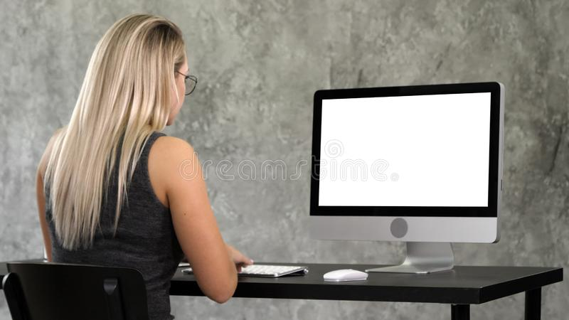 La ragazza dei pantaloni a vita bassa in vetri d'avanguardia si siede alla tavola davanti a funzionamento del computer Visualizza immagini stock