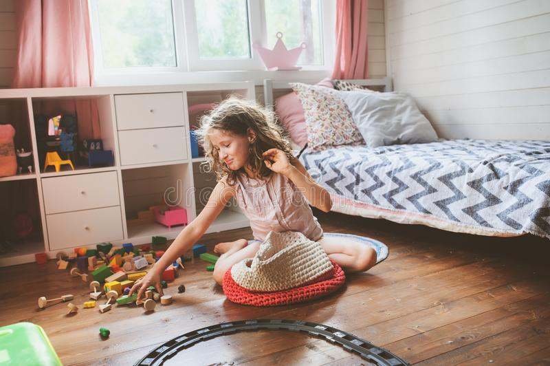 La ragazza del bambino che pulisce la sua stanza ed organizza i giocattoli di legno nella borsa tricottata di stoccaggio immagine stock libera da diritti