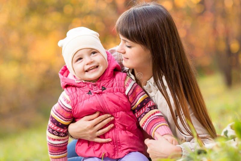 La ragazza del bambino e la giovane madre giocano nel parco di autunno immagini stock
