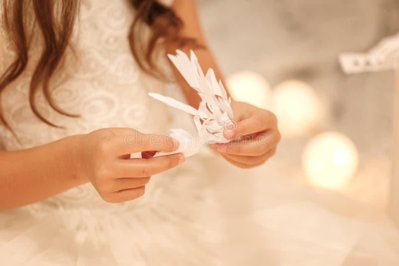 La ragazza del bambino fa i fiocchi di neve di carta per l'albero di Natale della decorazione fotografie stock