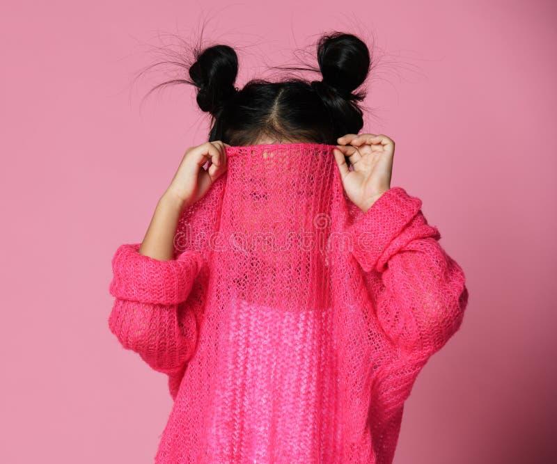 La ragazza del bambino nasconde il suo fronte in maglione rosa immagini stock libere da diritti