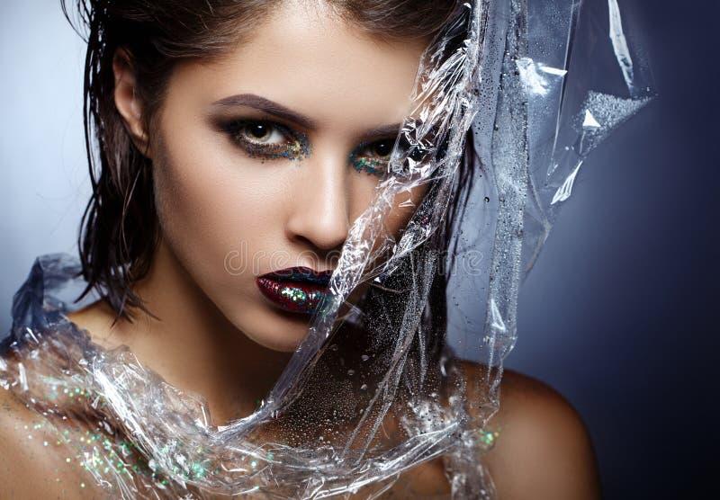 La ragazza del modello di moda di bellezza con luminoso compone Con la pellicola di polietilene fotografia stock libera da diritti
