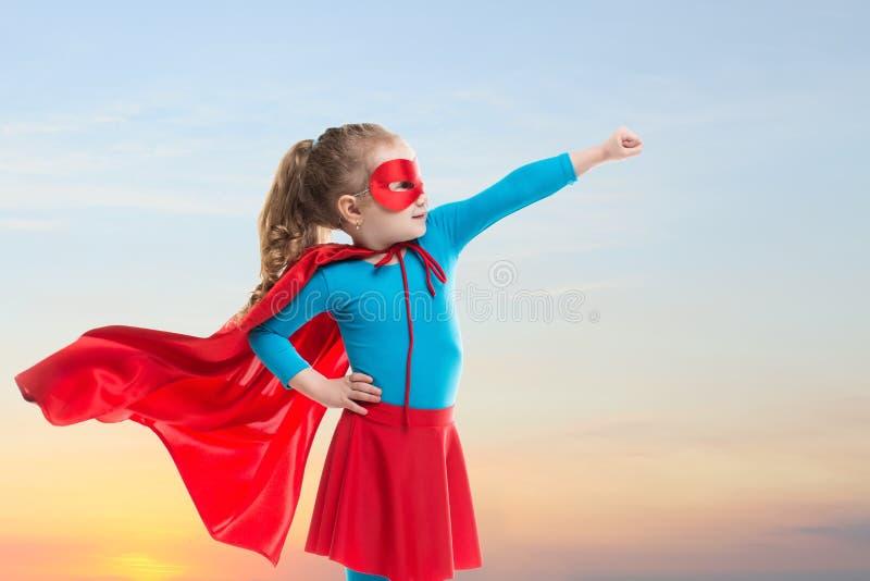 La ragazza del piccolo bambino gioca il supereroe Bambino sui precedenti del cielo di tramonto immagine stock libera da diritti