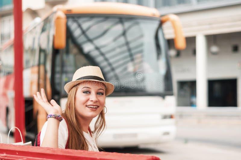 La ragazza del viaggiatore ondeggia la sua mano all'autostazione, aspettante la fotografie stock libere da diritti