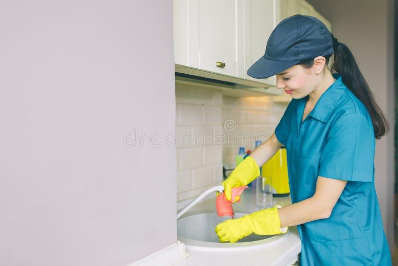 La ragazza deliziosa in cappuccio e uniforme sta e lavora al lavandino Sorride un pezzo La ragazza è pulitore professionale immagini stock libere da diritti