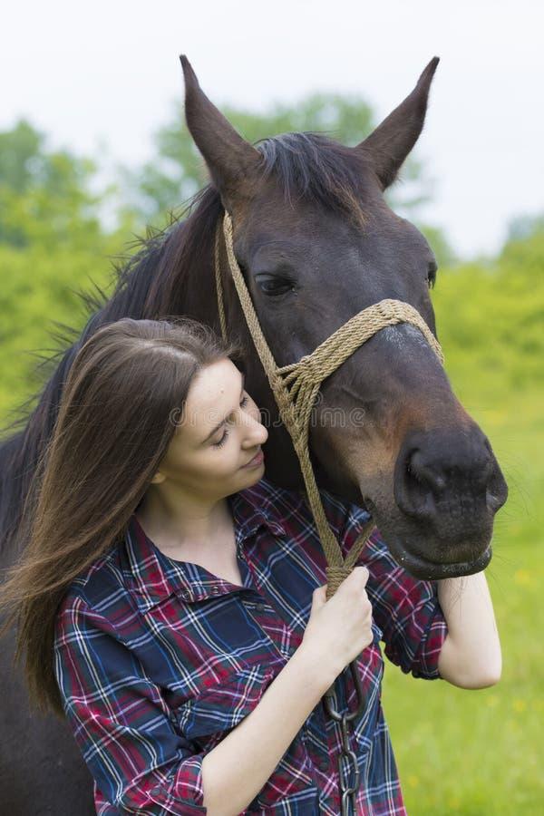 La ragazza dell'adolescente abbraccia il cavallo fotografia stock libera da diritti