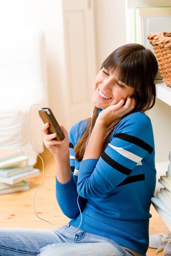 La ragazza dell'adolescente si distende a casa - felice ascolti musica fotografia stock