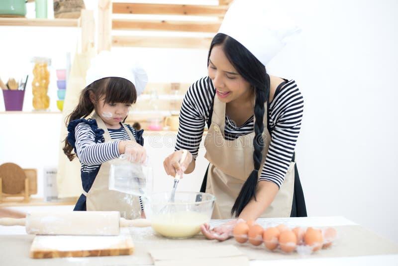 La ragazza della figlia del bambino e della madre sta cucinando i biscotti e divertiresi fotografia stock