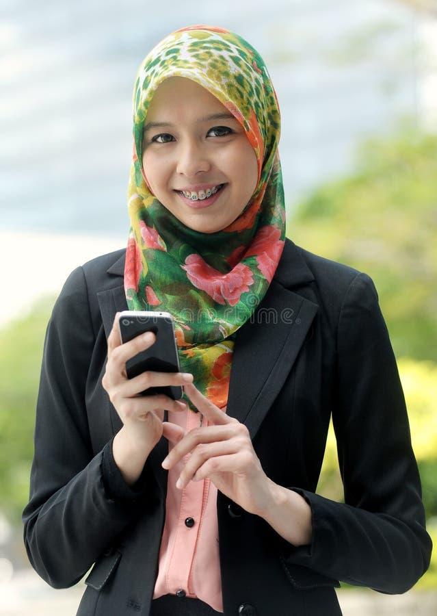 Ragazza della sciarpa che per mezzo del telefono astuto fotografia stock