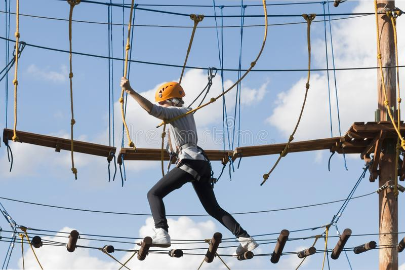 la ragazza della scuola scala in un parco della corda di avventura fotografie stock libere da diritti