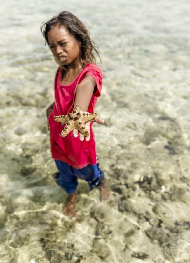 La ragazza della tribù di Bajau ha preso il pesce della stella dal mare e la prova vendere quello al turista, Sabah Semporna, Mal fotografia stock