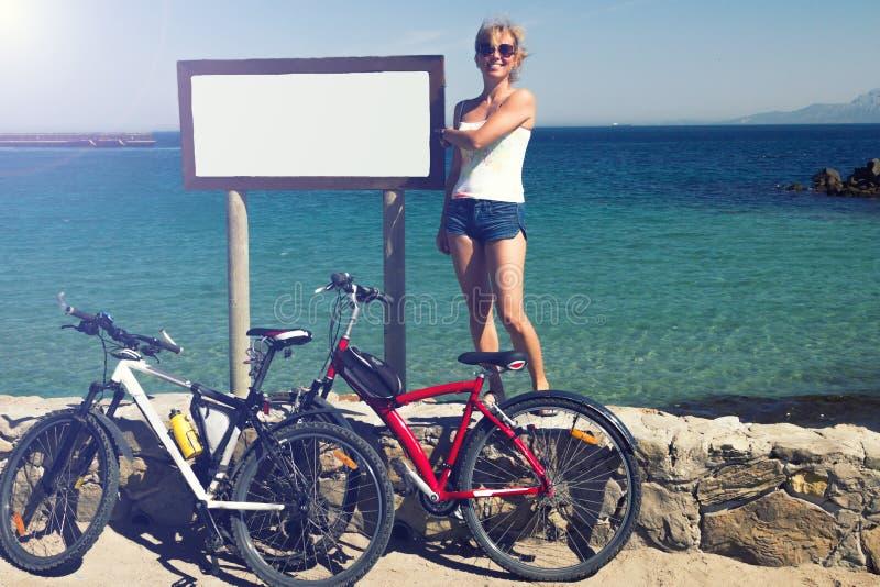 La ragazza delle donne invecchiata mezzo resta con due biciclette al coastl della spiaggia fotografia stock libera da diritti