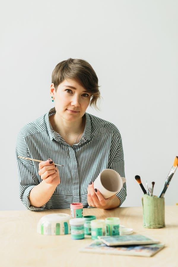 La ragazza delle terraglie tiene in mani una tazza per dipingere l'ornamento fotografia stock libera da diritti