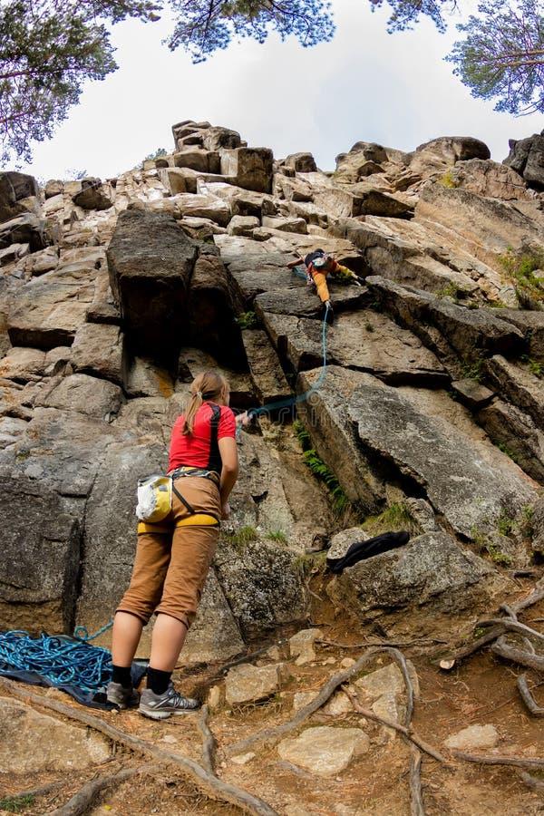 La ragazza dello scalatore assicura un uomo dello scalatore su una scogliera con assicurazione più bassa immagini stock