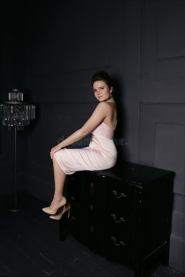 La ragazza dentro grugnisce il vestito che si siede su un cassetto in una stanza scura immagini stock libere da diritti