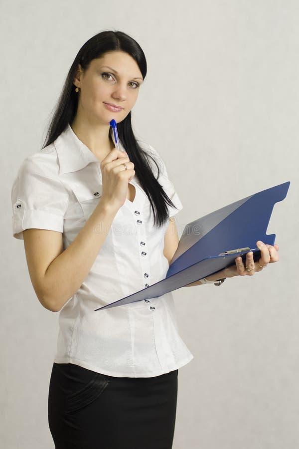 La ragazza di affari ascolta e fa le note in una cartella fotografia stock