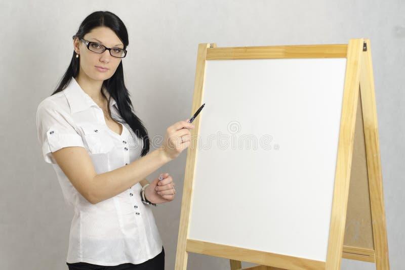 La ragazza di affari con i vetri mostra un indicatore su un bordo bianco immagini stock libere da diritti
