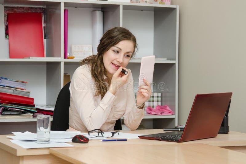 La ragazza di affari dipinge le labbra con rossetto nell'ufficio fotografia stock