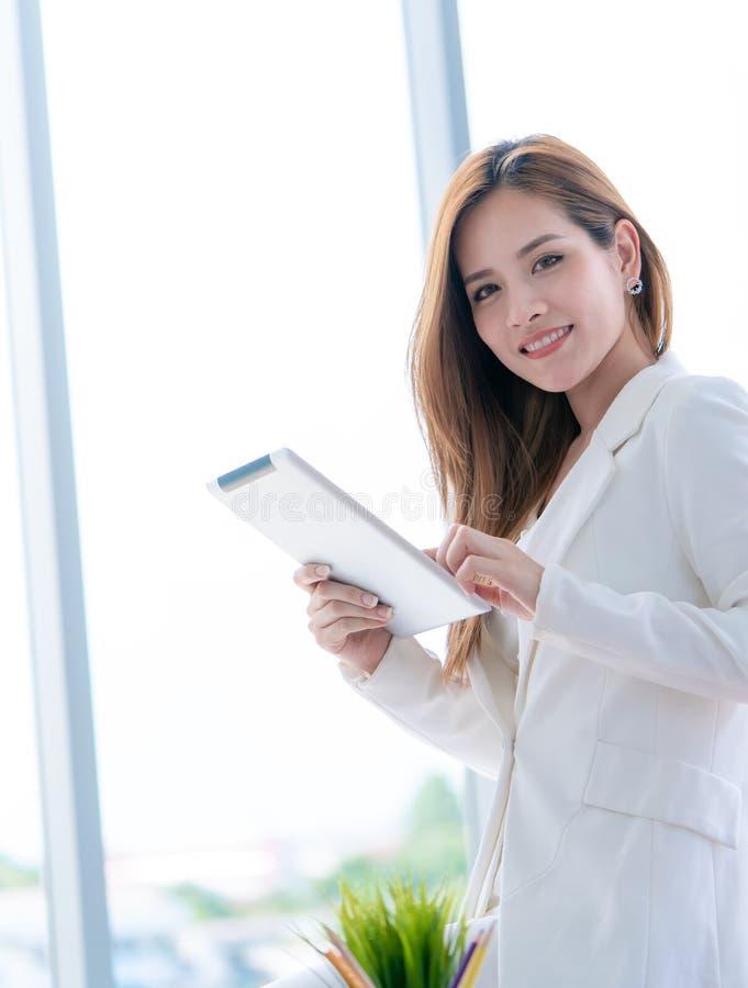 La ragazza di affari sta controllando il rapporto sulla compressa fotografie stock