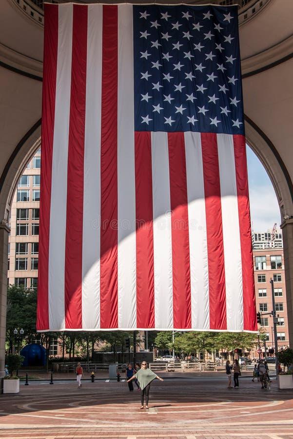 04 09 La ragazza 2017 di Boston Massachusetts U.S.A. che sta sotto grandi bande americane delle stelle inbandiera pendere dalla c fotografie stock libere da diritti
